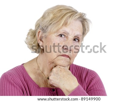 Portrait of a serious senior woman holding her chin looking at the camera, isolated on white. - stock photo