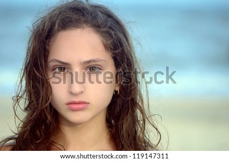 Portrait of a serious teen girl on the beach - stock photo