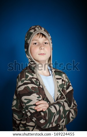 portrait of a serious teenage boy on a blue background - stock photo