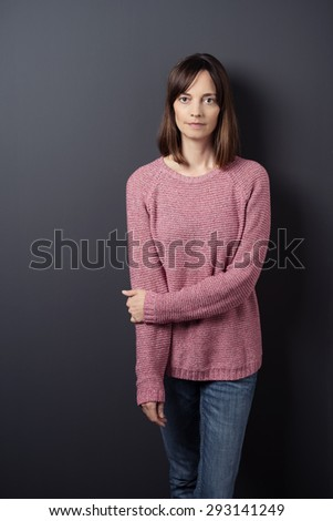 Portrait of a Serious Woman in Trendy Clothing, Standing Against Gray Wall While Holding her Other Arm and Looking Straight at the Camera. - stock photo