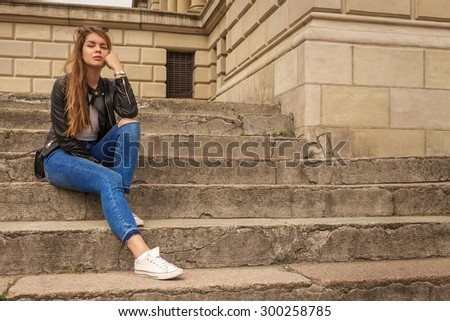 Portrait of a serious woman thinker sitting on steps