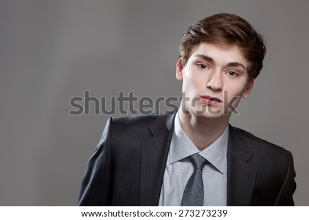Portrait of a serious young business man on gray background - stock photo