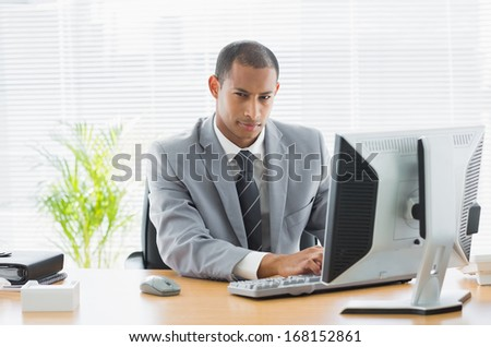 Portrait of a serious young businessman using computer at office desk