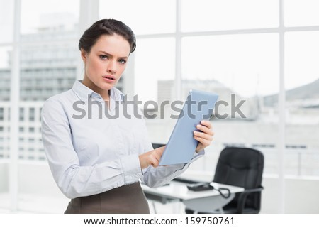 Portrait of a serious young businesswoman using table PC in a bright office