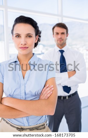 Portrait of a serious young businesswoman with male colleague in background at a bright office