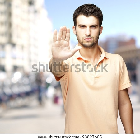 portrait of a serious young man doing a stop symbol against a crowded street - stock photo