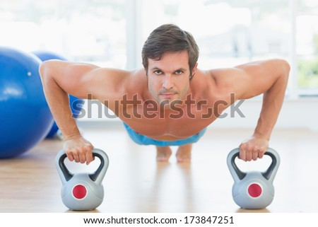 Portrait of a serious young man doing push ups in the bright gym - stock photo