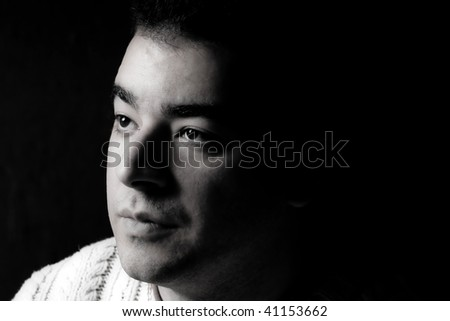Portrait of a serious young man in dramatic lighting. - stock photo