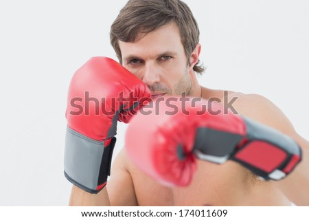 Portrait of a serious young man in red boxing gloves over white background - stock photo