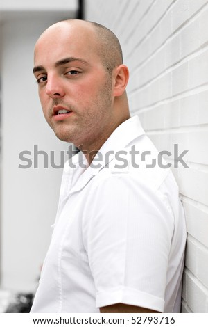 Portrait of a serious young man in the city leaning against a white brick wall. - stock photo