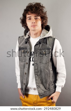 Portrait Of A Serious Young Man Standing On Grey Background - stock photo