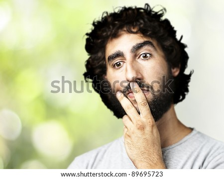 portrait of a serious young man thinking against a nature background - stock photo