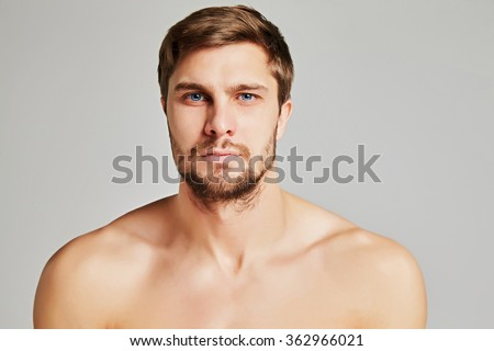 Portrait of a serious young man with bare shoulders on a gray background, powerful swimmers shoulders, beard, charismatic, adult, brutal, athletic, edited photo - stock photo