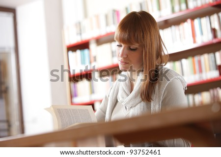 Portrait of a serious young student reading a book in a library - stock photo