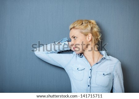 Portrait of a serious young woman looking away against blue background - stock photo