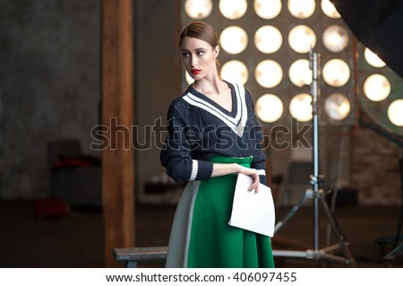 Portrait of a serious young woman standing backstage with her scripts wearing black sweater and green skirt - stock photo