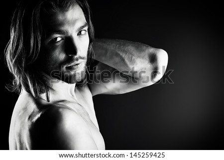 Portrait of a sexual muscular nude man posing over dark background. - stock photo