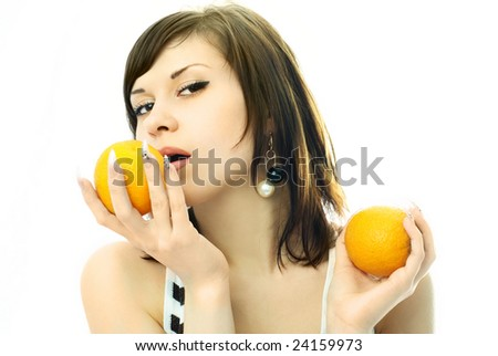 portrait of a sexy beautiful brunette woman eating oranges - stock photo