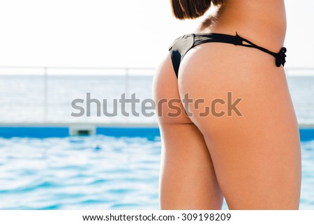 Portrait of a sexy female hips with swim pool on background - stock photo