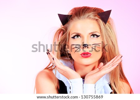 Portrait of a sexy girl in pussycat costume alluring over pink background. - stock photo