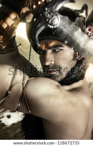 Portrait of a sexy male model as ancient warrior with sword and helmet - stock photo