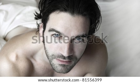 Portrait of a sexy man relaxed in bed - stock photo