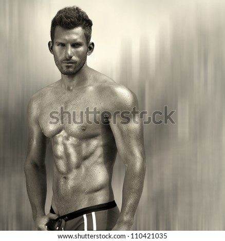 Portrait of a sexy muscular male model against modern abstract metallic background with copy space - stock photo