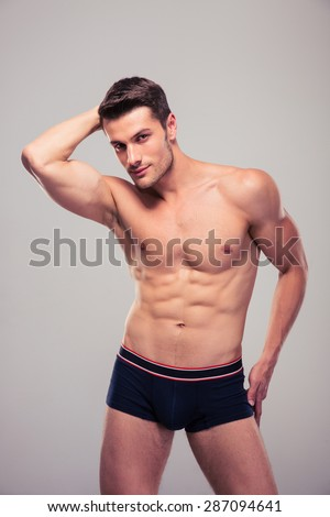 Portrait of a sexy muscular man posing over gray background. Looking at camera - stock photo