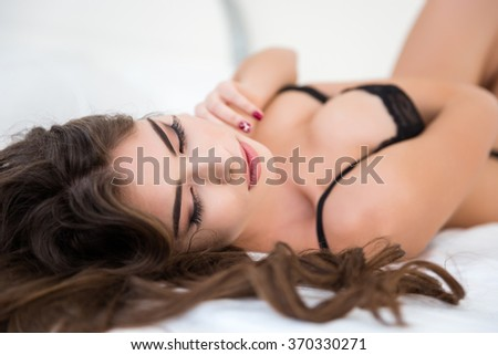 Portrait of a sexy relaxed woman in lingerie lying on the bed - stock photo