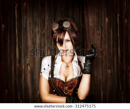 Portrait of a sexy steampunk woman with big breast wearing vintage corset and retro goggles on old wooden background
