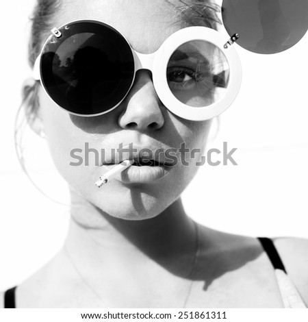 portrait of a  sexy woman in sunglasses with cigarette. Toned black and white. White background, not isolated - stock photo