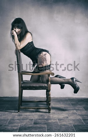 Portrait Of A Sexy Woman Leaning On Wooden Chair - stock photo