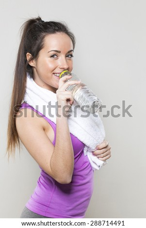 portrait of a sexy young athletic woman with towel around her neck drinking water for hydration after gym exercise - stock photo