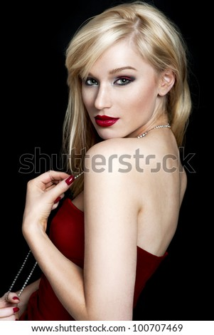 Portrait of a sexy young blond woman in a red dress on black background