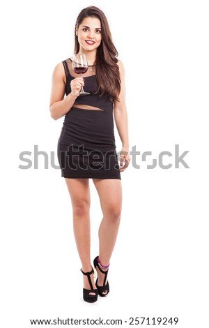 Portrait of a sexy young Latin woman in a black dress holding a glass of red wine on a white background