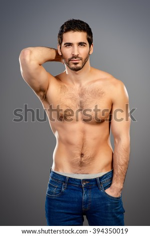 Portrait of a sexy young man with perfect muscular body slightly smiling invitingly at camera. Gray background. Studio shot. - stock photo