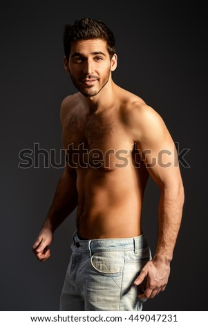 Portrait of a sexy young man with perfect muscular body smiling invitingly at camera. Black background. Studio shot.