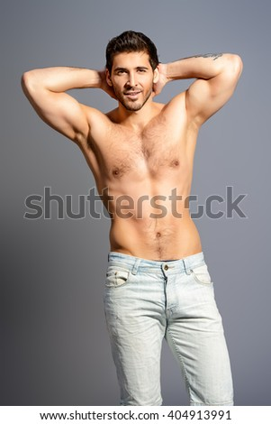 Portrait of a sexy young man with perfect muscular body smiling invitingly at camera. Gray background. Studio shot. - stock photo