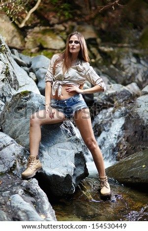Portrait of a sexy young woman standing on the mountain rocks