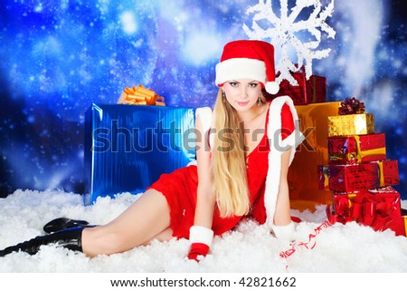 Portrait of a sexy young woman wearing christmas clothes over sky of stars and snow. - stock photo