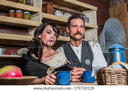 Portrait of a sheriff and his wife inside of house - stock photo