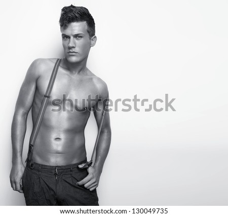 Portrait of a shirtless sexy man with suspenders leaning against white wall - black and white - stock photo