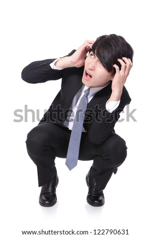 Portrait of a shocked and scared business man and crouch on the floor isolated on white background - stock photo