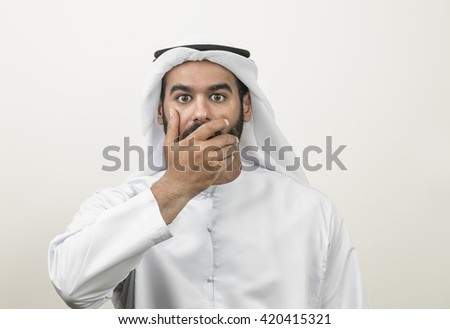Portrait of a shocked Arabian man covering his mouth , Arabian guy shocked - stock photo