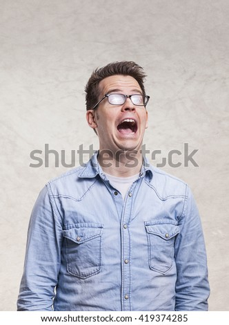 Portrait of a shocked, screaming, stunned or surprised young man -  isolated on light gray wall background - stock photo