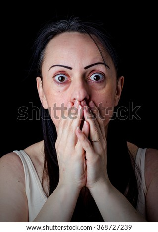 Portrait of a shocked worried woman covering her mouth with her hands. - stock photo
