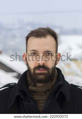 Portrait of a shocked young bearded man in the winter scenery - stock photo