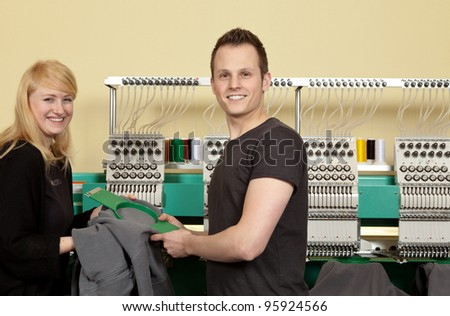 Portrait of a shop assistant and a Young Man in her Textile embroidery Shop - stock photo