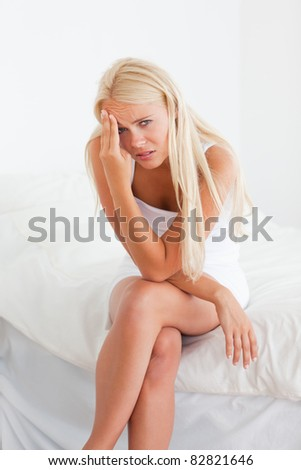 Portrait of a sick blonde woman sitting on her bed