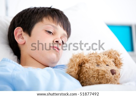 Portrait of a sick boy hugging a teddy bear lying in a hospital bed